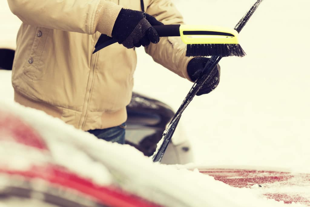 scraping snow off windshield in winter