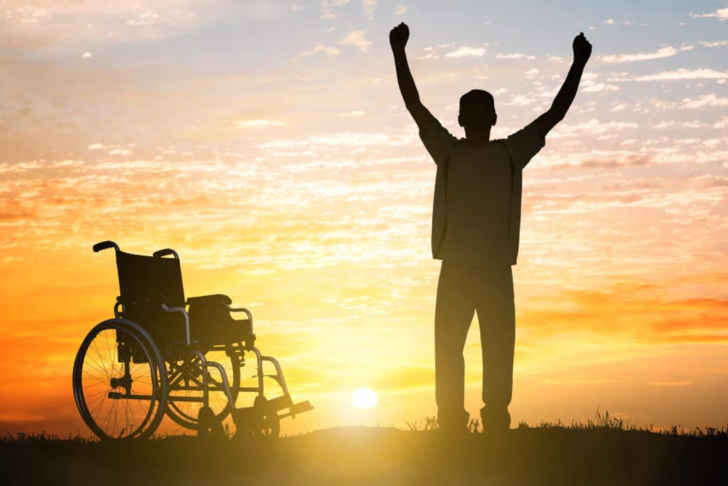 man standing with wheelchair behind him, celebrating