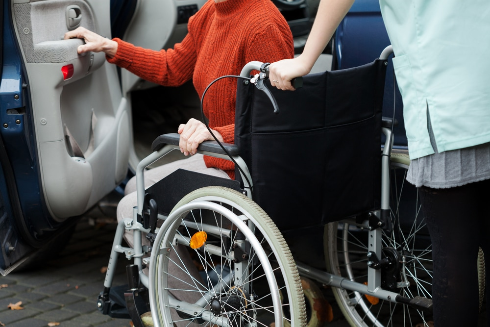 physically impaired person being assisted by woman