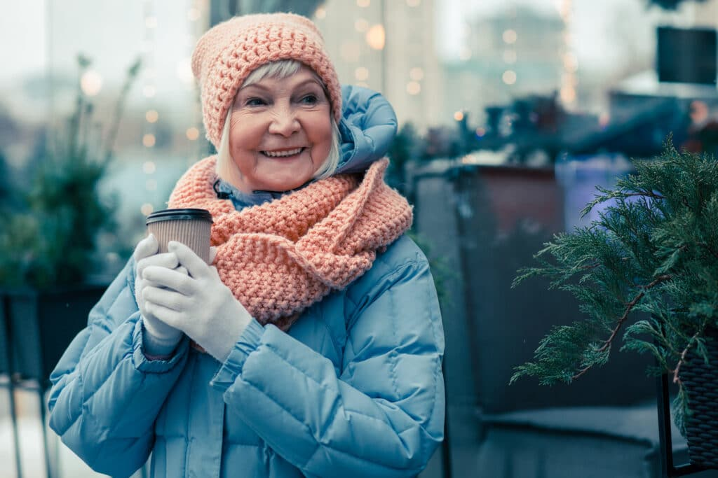 Cheerful aged woman spending time outdoors in a cold winter day and smiling while holding a cup of coffee