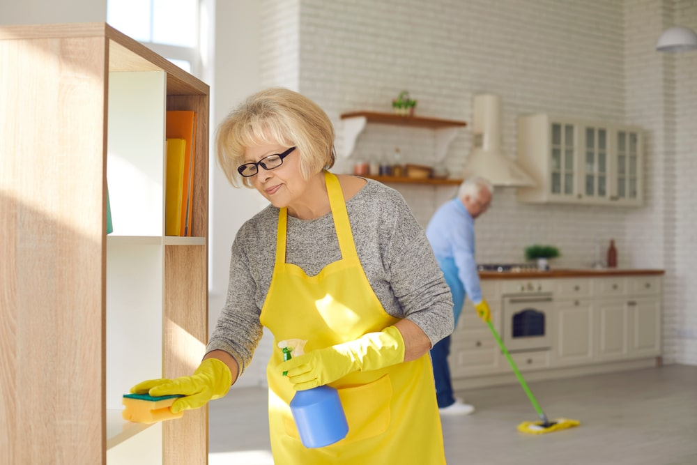 Elderly couple wearing bright yellow cleaning their kitchen