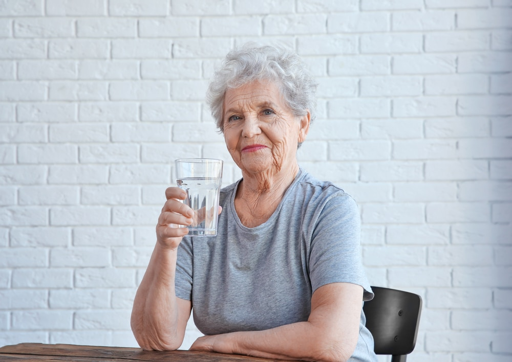 Elderly woman sitting and drinking a glass of water at table.