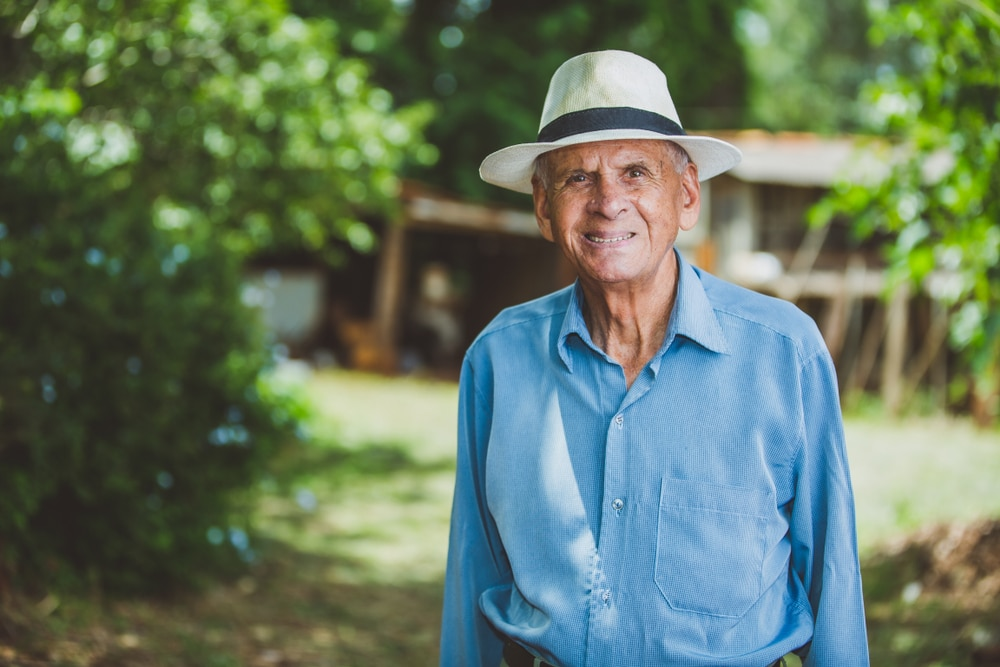 Elderly man at farm on a summer day wearing a hat for skin protection.