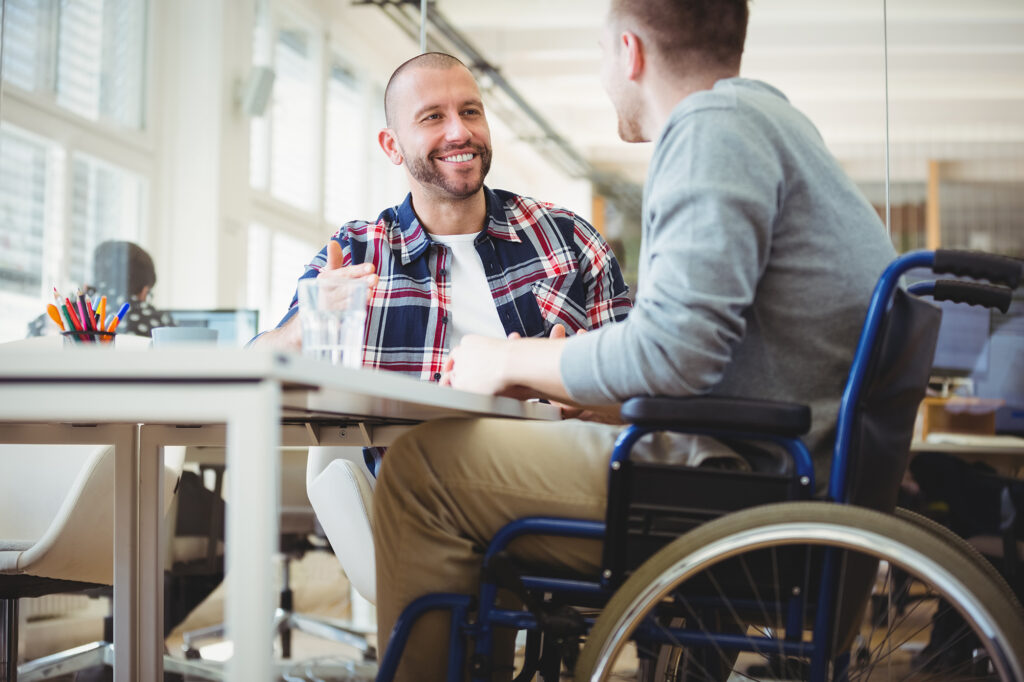 Working with people with disabilities. Handicap businessman discussing while sitting with colleague in creative office.